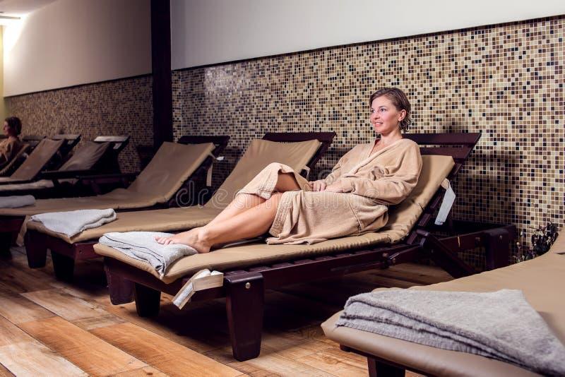 放松和enjoing她的在温泉沙龙的美丽的年轻女人时间 免版税库存图片