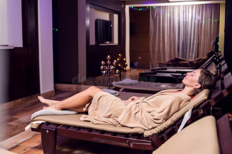 放松和enjoing她的在温泉沙龙的美丽的年轻女人时间 图库摄影