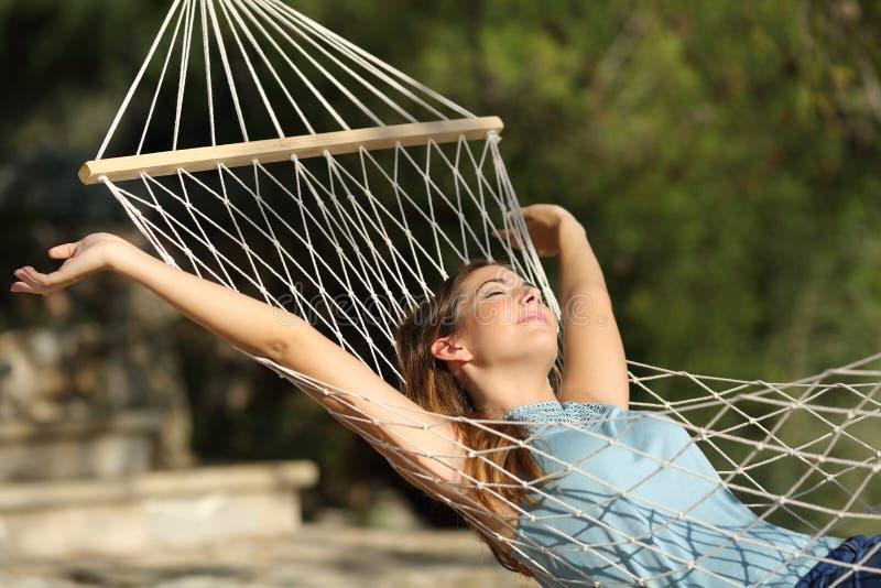 放松在一个吊床在度假和举胳膊的愉快的妇女 免版税库存照片