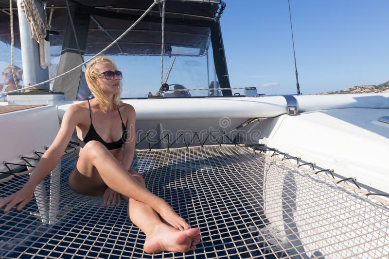 放松在一个夏天的美女航行巡航,在和晒日光浴在航行豪华筏的吊床  库存照片