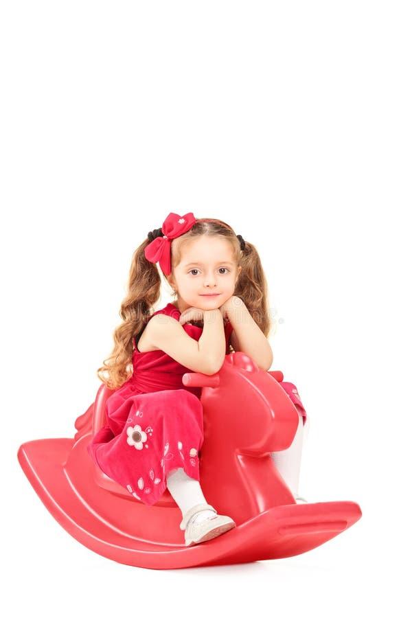 放松在一个晃动的玩具的一件红色礼服的小女孩 免版税库存图片
