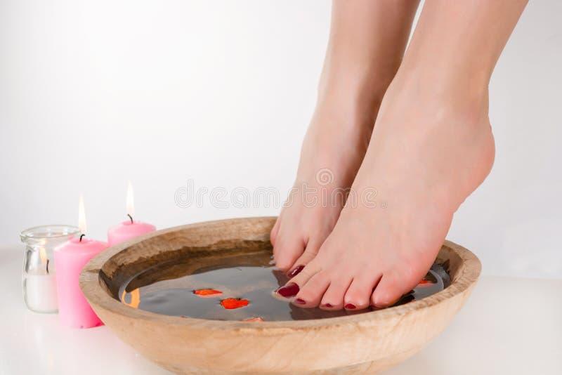 放松在一个木碗的水中的年轻女人脚 库存照片