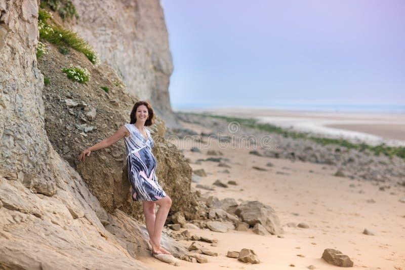 放松在一个美丽的海滩的可爱的孕妇 图库摄影