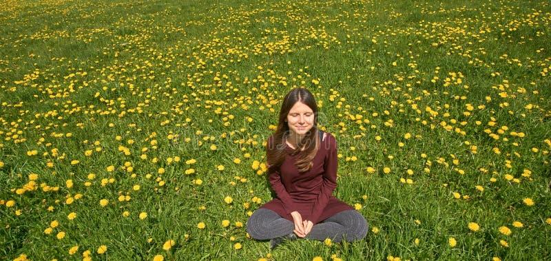 放松在一个草甸的美丽的微笑的少妇用许多蒲公英在春天太阳 与copyspace的前面视图 免版税库存照片