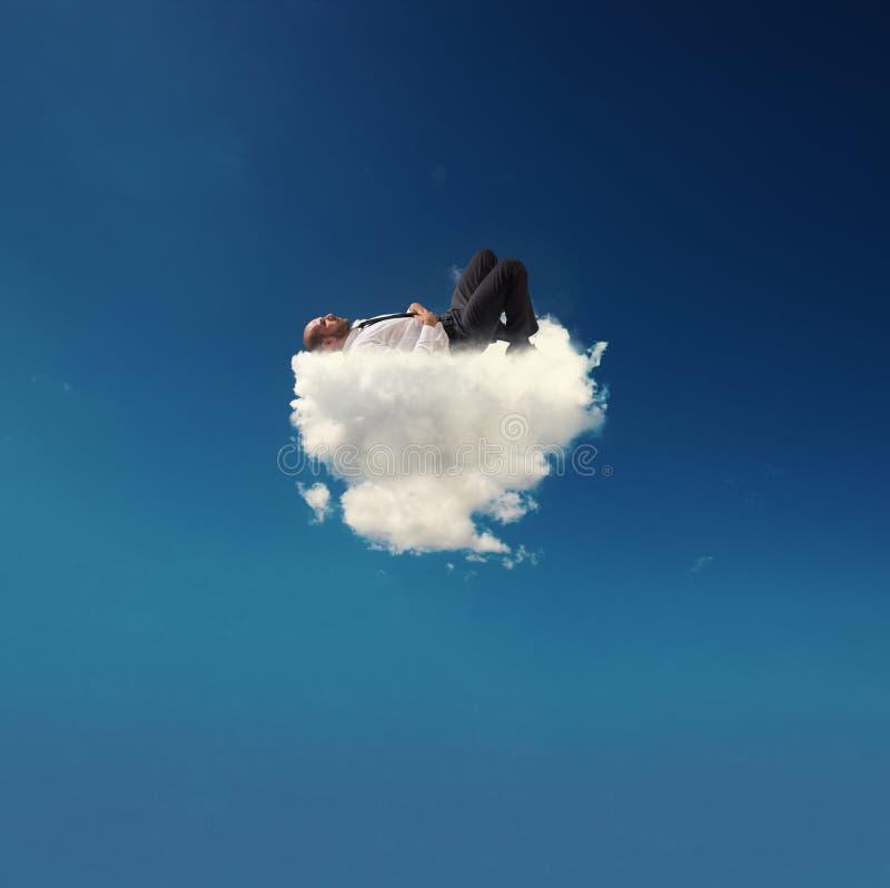放松在一朵软的云彩的被注重的商人 免版税库存照片