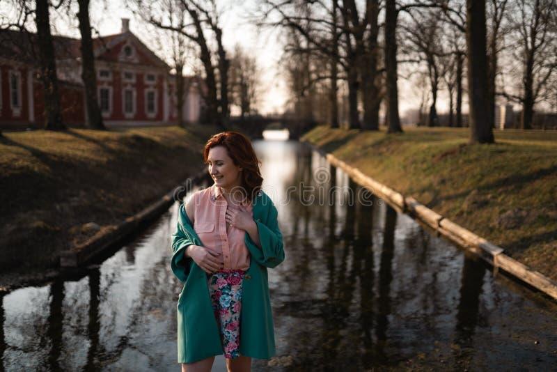 放松在一条运河河附近的美丽的年轻女人在公园在宫殿附近在Rundale,拉脱维亚,2019年 免版税库存图片