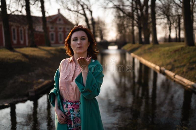 放松在一条运河河附近的美丽的年轻女人在公园在宫殿附近在Rundale,拉脱维亚,2019年 图库摄影