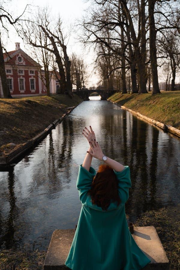 放松在一条运河河附近的美丽的年轻女人在公园在宫殿附近在Rundale,拉脱维亚,2019年 库存图片