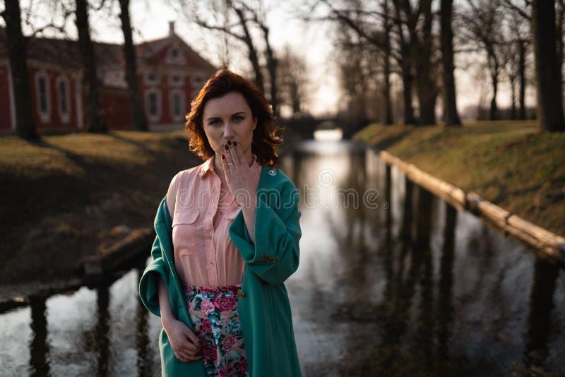 放松在一条运河河附近的美丽的年轻女人在公园在宫殿附近在Rundale,拉脱维亚,2019年 免版税图库摄影