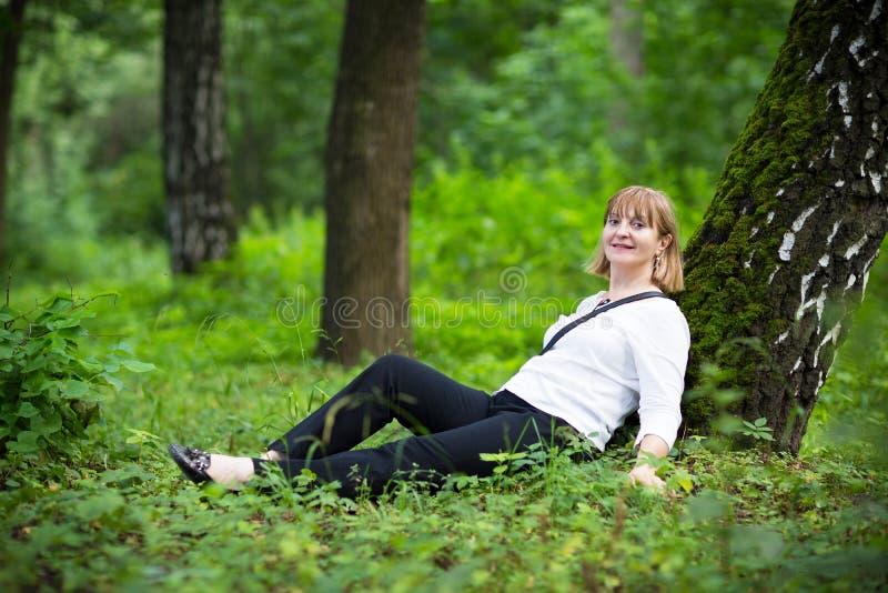 放松在一棵大老树下的美丽的妇女 库存图片