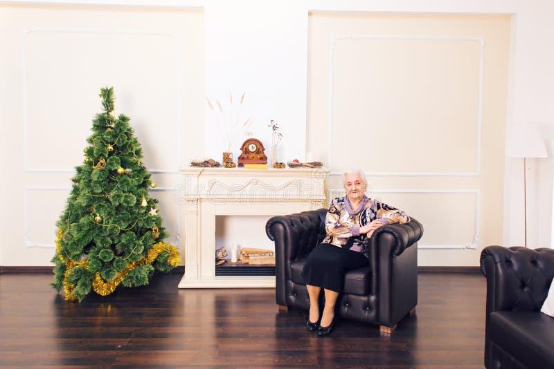 放松在一棵装饰的圣诞树前面的微笑的年长妇女在她的客厅 库存照片