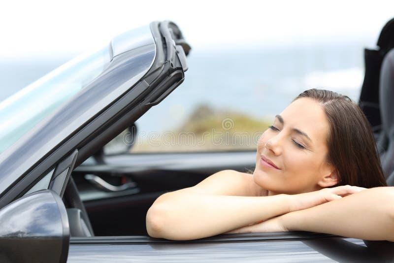 放松在一辆敞篷车汽车的女孩在度假 库存图片