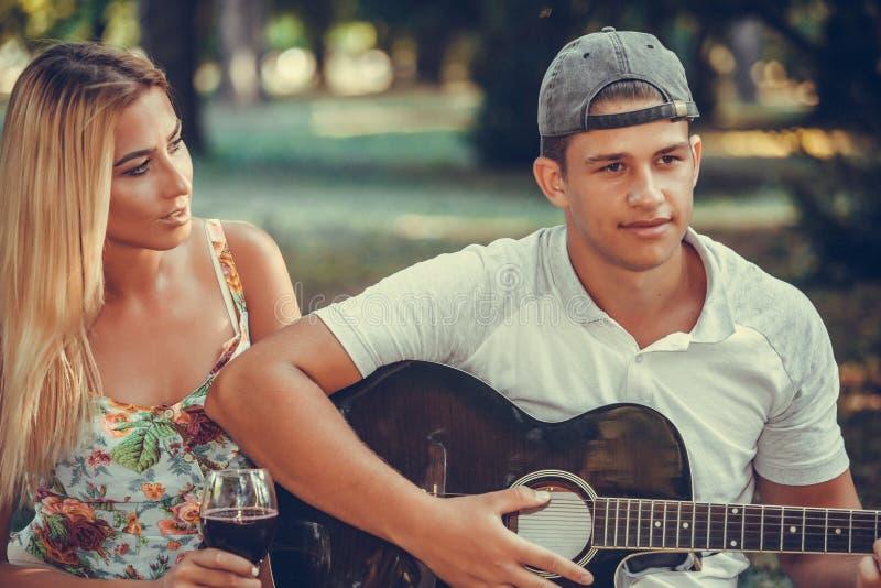 放松在一顿野餐的愉快的年轻夫妇本质上 图库摄影