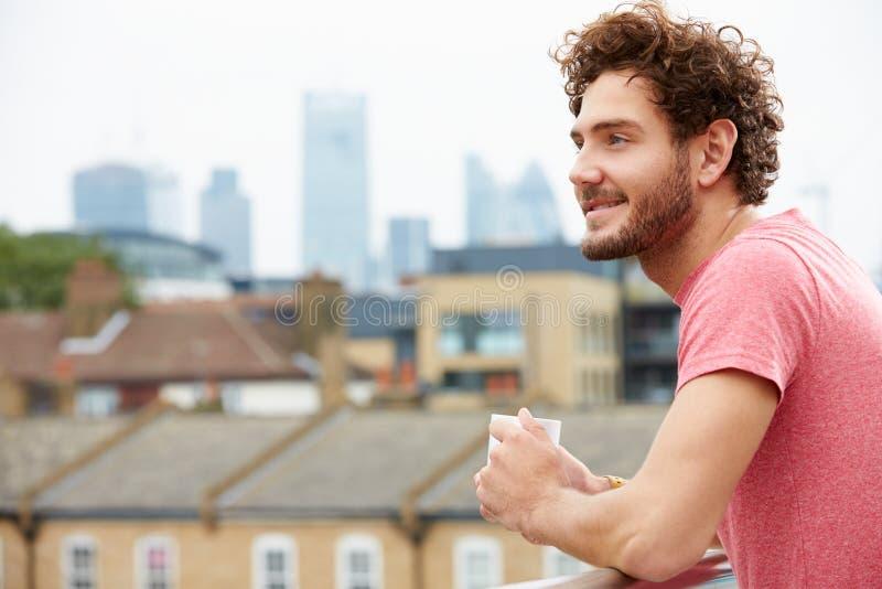 放松在与咖啡的屋顶大阳台的年轻人 图库摄影
