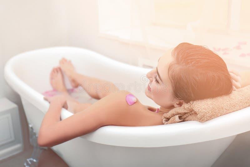 放松在与泡沫的浴的年轻可爱的妇女 免版税库存照片