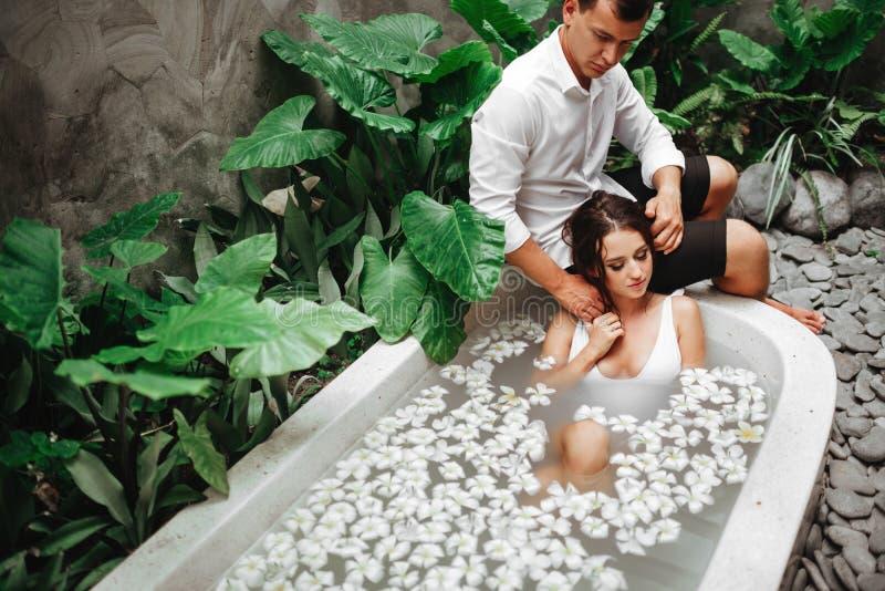 放松在与热带花的浴的妇女和人室外在豪华旅馆手段 免版税库存图片