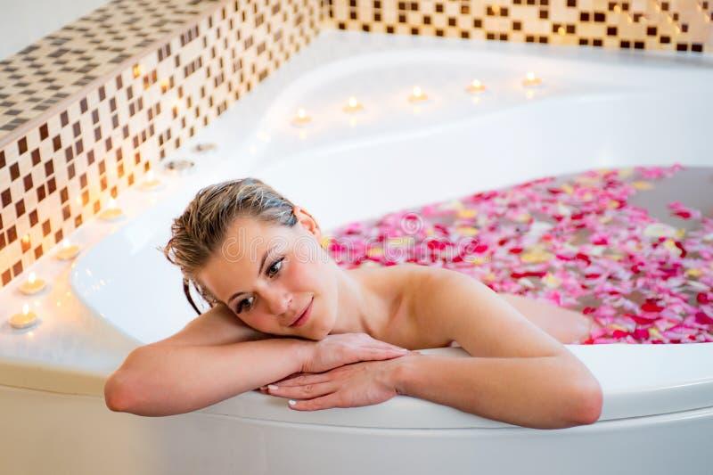放松在与玫瑰花瓣的浴的一个可爱的女孩 免版税库存照片