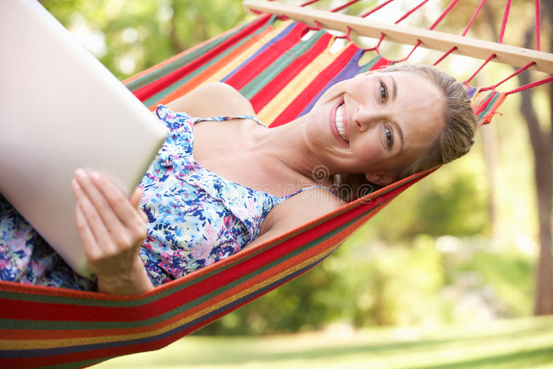 放松在与膝上型计算机的吊床的妇女 免版税图库摄影