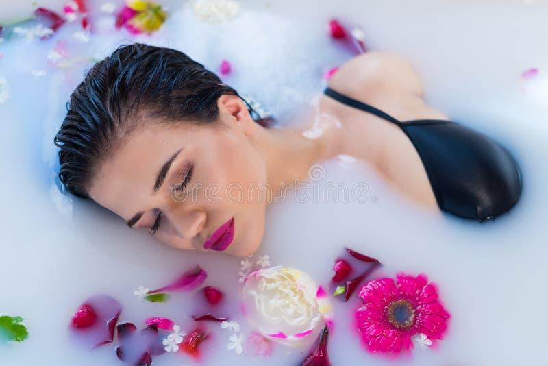 放松在与花的热的牛奶浴的性感的深色的妇女 免版税库存图片