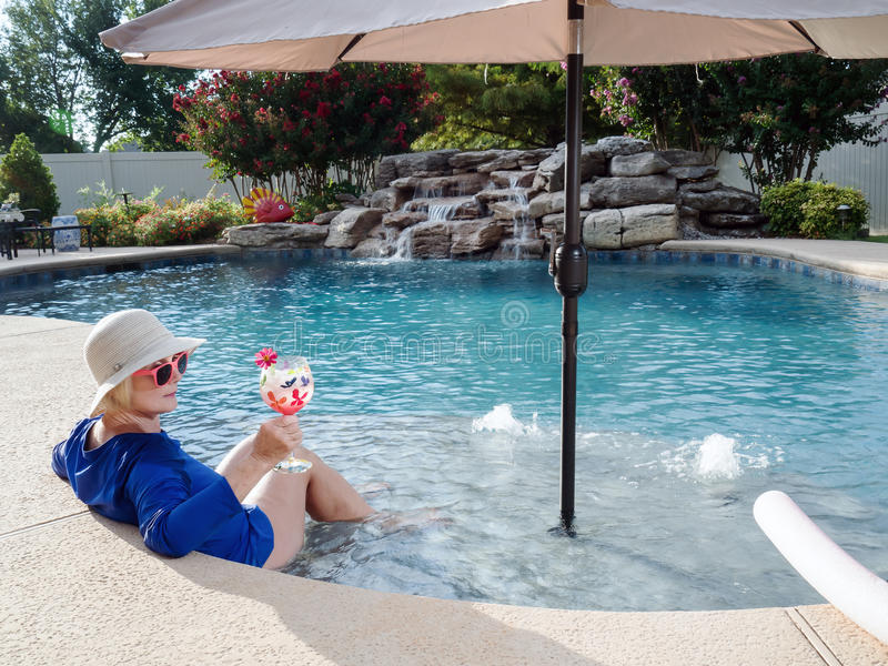 放松在与饮料的水池的妇女 免版税图库摄影