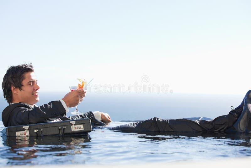 放松在与鸡尾酒的一个游泳池的新生意人 免版税图库摄影