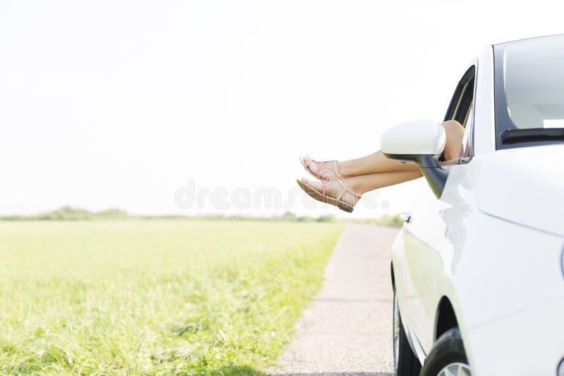 放松在乡下公路的汽车的妇女的低部分 免版税库存照片