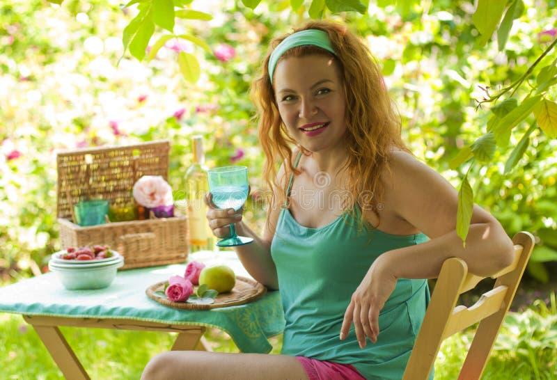 放松在乡间别墅和饮用水里的愉快的妇女 库存图片
