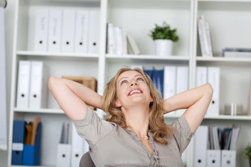 放松在书桌的女实业家 免版税图库摄影