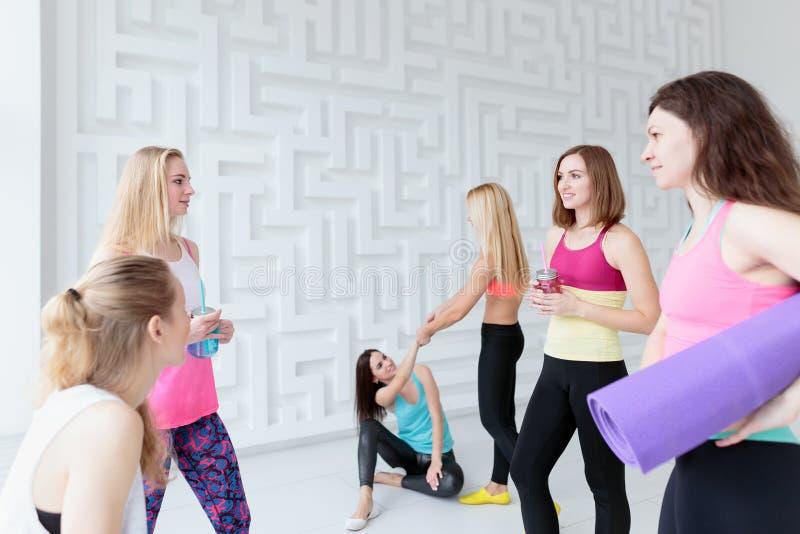 放松在他们的锻炼以后的运动的妇女在瑜伽演播室 免版税库存图片