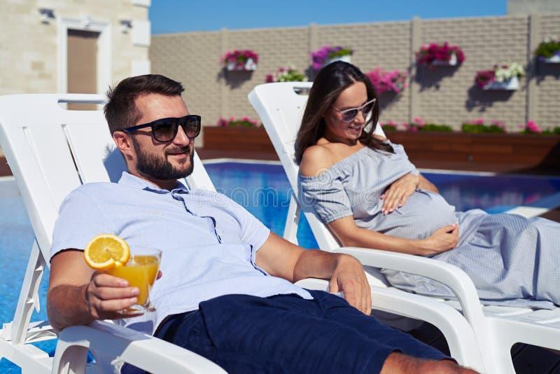 放松在休息室的丈夫和怀孕的妻子在水池附近 库存照片