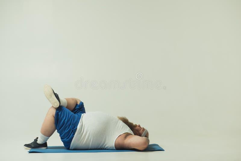 放松在体育地毯的慢吞吞的厚实的人 图库摄影