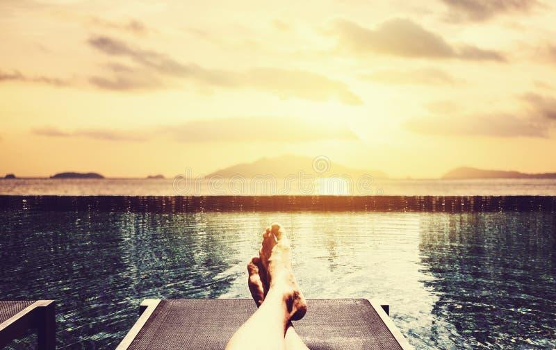 放松在假日,人在游泳池边晒日光浴在热带海滩胜地在夏天 免版税库存照片