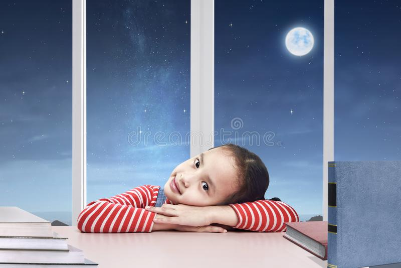 放松在做的愉快的亚裔女孩家庭作业以后 免版税库存图片