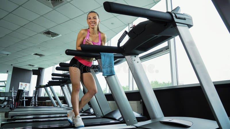 放松在健身俱乐部的踏车的年轻微笑的妇女 免版税库存照片
