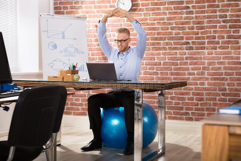 放松在健身球的愉快的商人在办公室 图库摄影
