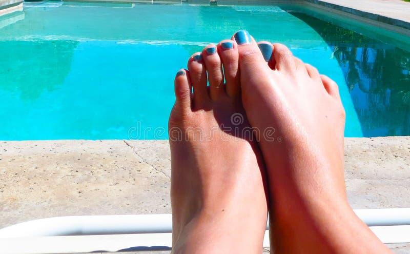 放松在充满活力的水池旁边的Pedicured脚 免版税库存照片