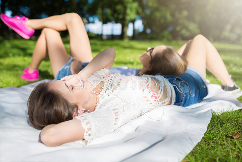 放松在公园听的音乐的两名俏丽的妇女 库存照片