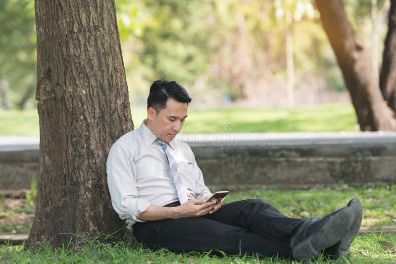 放松在公园的亚裔商人在工作以后 看p的他 库存照片