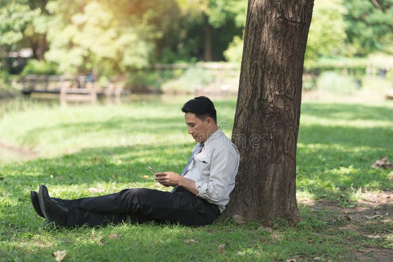 放松在公园的亚裔商人在工作以后 看p的他 免版税图库摄影