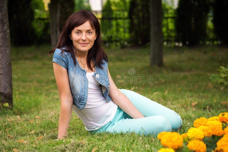 放松在公园的愉快的妇女 户外美丽的少妇 享受本质 春天草甸的健康微笑的女孩 美丽的L.A.在晚上 库存图片