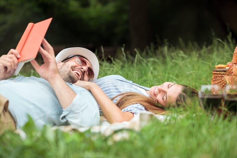 放松在公园的愉快的微笑的年轻夫妇 说谎在野餐毯子 免版税库存照片
