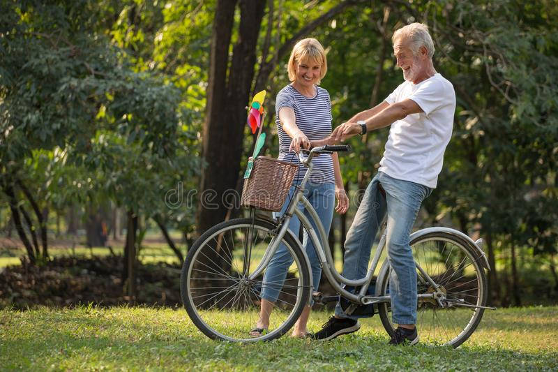 放松在公园的愉快的资深夫妇走与自行车和一起谈话在早晨时间 老人在秋天公园 免版税库存照片