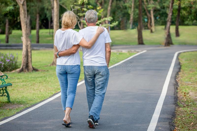 放松在公园的愉快的资深爱恋的夫妇一起拥抱和走在早晨时间 享用的老人拥抱和 库存照片