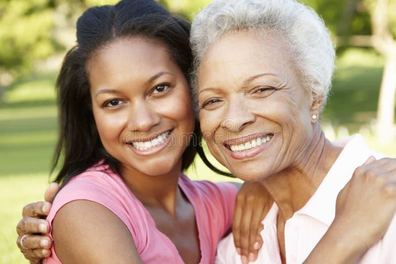 放松在公园的非裔美国人的母亲和成人女儿 免版税库存图片