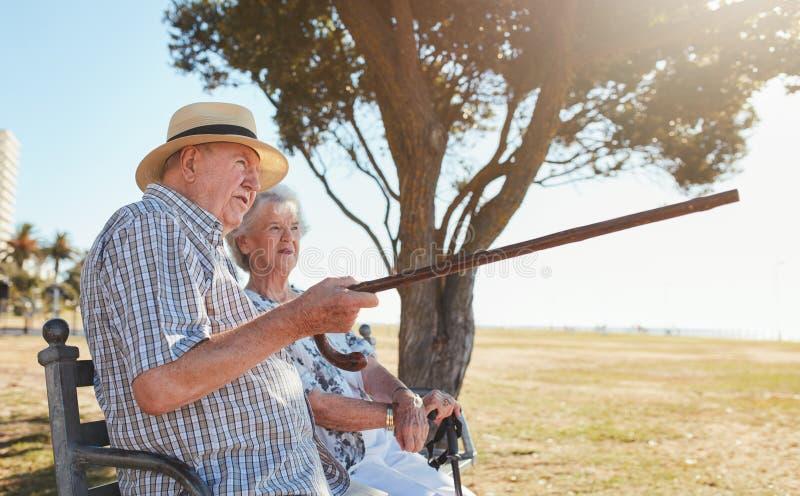 放松在公园长椅和享受看法的资深夫妇 免版税库存照片