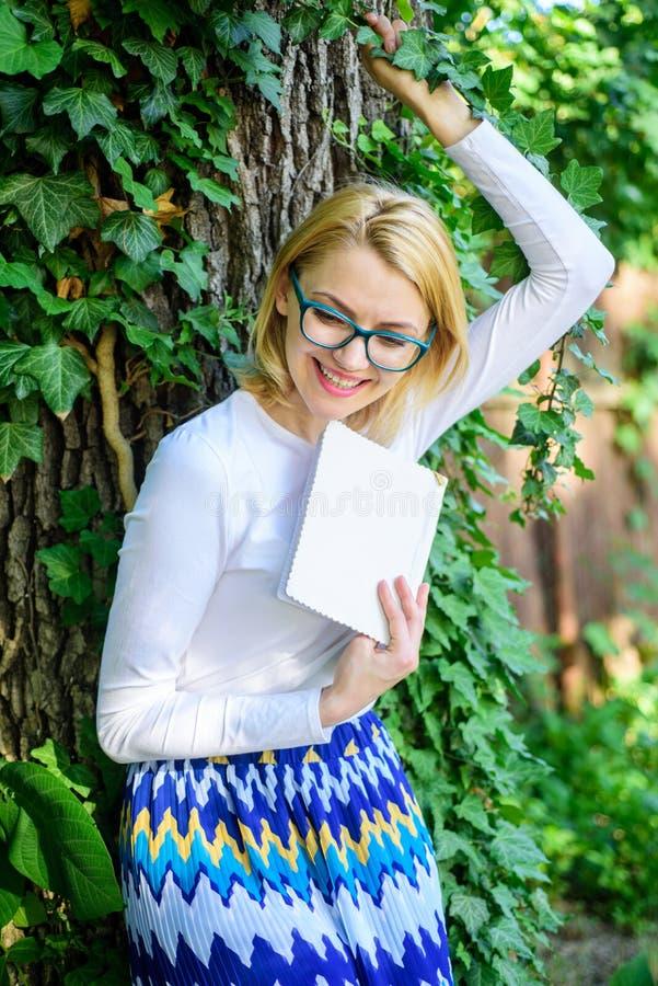 放松在公园阅读书的妇女白肤金发的作为断裂 夫人快乐的笑她喜欢滑稽可笑的故事 书痴学生 免版税库存照片