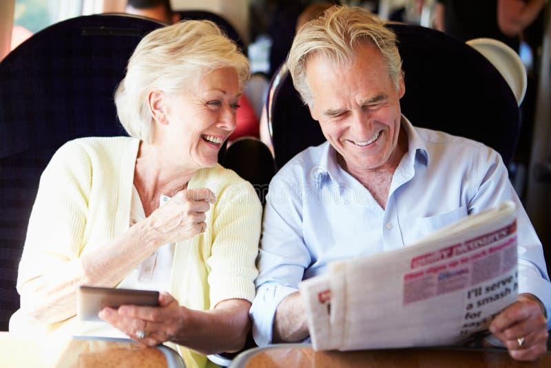 放松在列车行程上的资深夫妇 库存照片