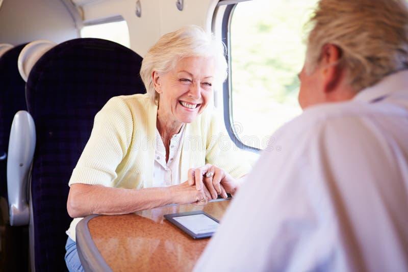 放松在列车行程上的资深夫妇 免版税库存图片