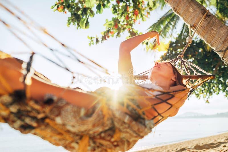 放松在吊床取决于在棕榈树之间和使用与太阳光芒的粗心大意的白肤金发的长发妇女 库存图片