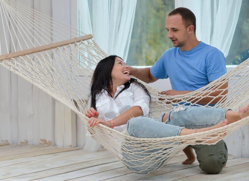 放松在吊床微笑和人身分的妇女 免版税库存图片